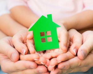 family-holding-green-house